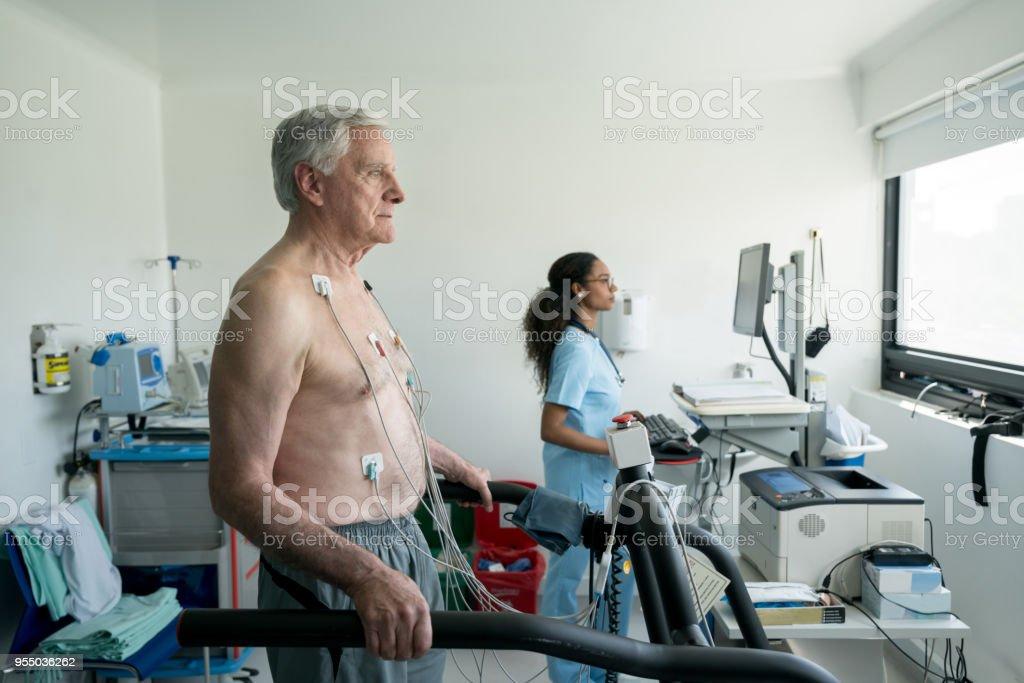 Senior man on a treadmill doing a stress test at the hospital while black nurse looks at the cardiac monitor stock photo