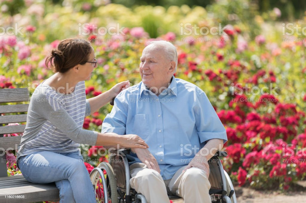 Senior man on a wheelchair and home caregiver, walking outdoors