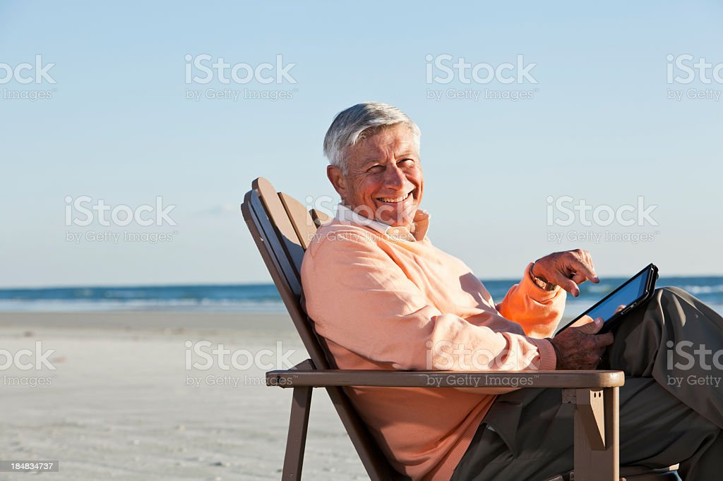 Senior man on beach using digital tablet royalty-free stock photo