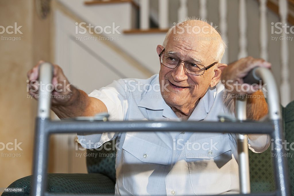 Senior man on couch with walker stock photo