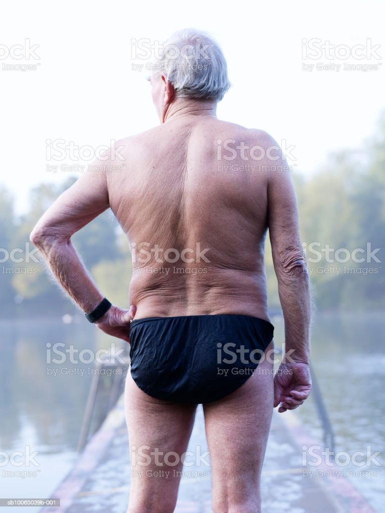 Senior man on diving board, rear view royalty-free stock photo