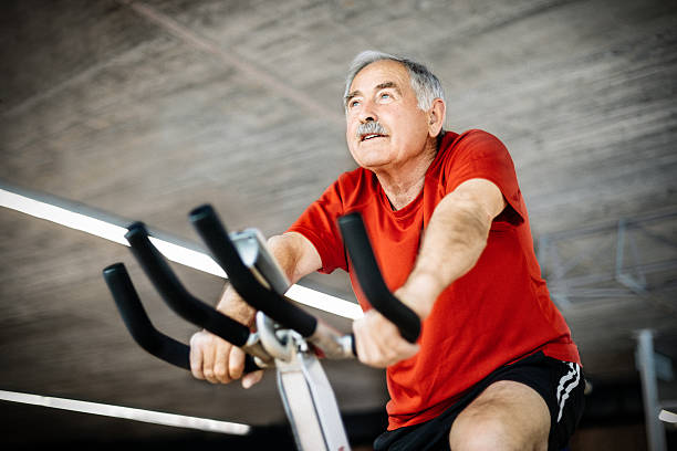 Senior Man on exercising Bicycle Healthy senior man in GYM cycling on exercising bicycle exercise bike stock pictures, royalty-free photos & images