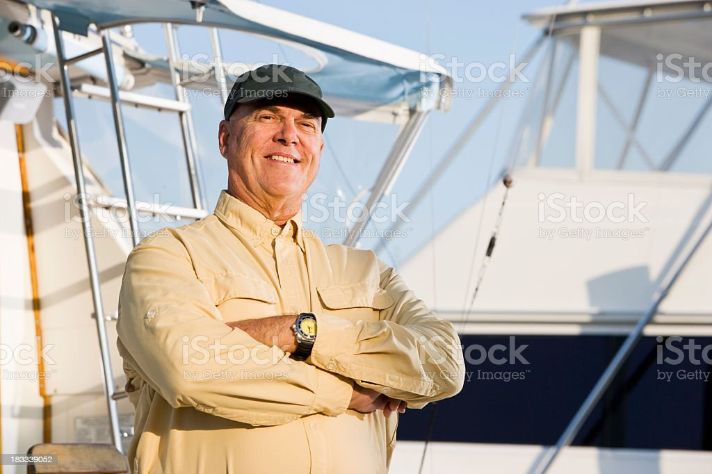 Senior man on fishing boat in marina royalty-free stock photo
