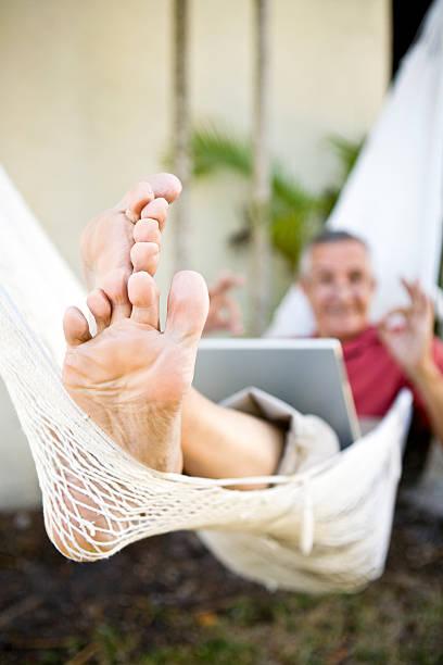 senior man on hammock gesturing okay focus on feet - old man feet stock photos and pictures