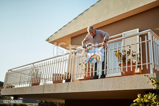 Senior man on his 70s fixing rainbow drawing at balcony during quarantine. He is showing his support for all the workers and helpers who are helping during the COVID-19 outbreak.