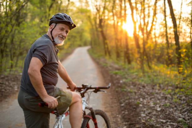 uomo anziano sulla sua mountain bike all'aperto - ciclismo foto e immagini stock
