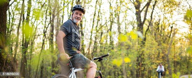 istock Senior man on his mountain bike outdoors 518659200