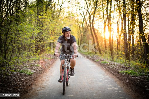 518659854istockphoto Senior man on his mountain bike outdoors 518659520