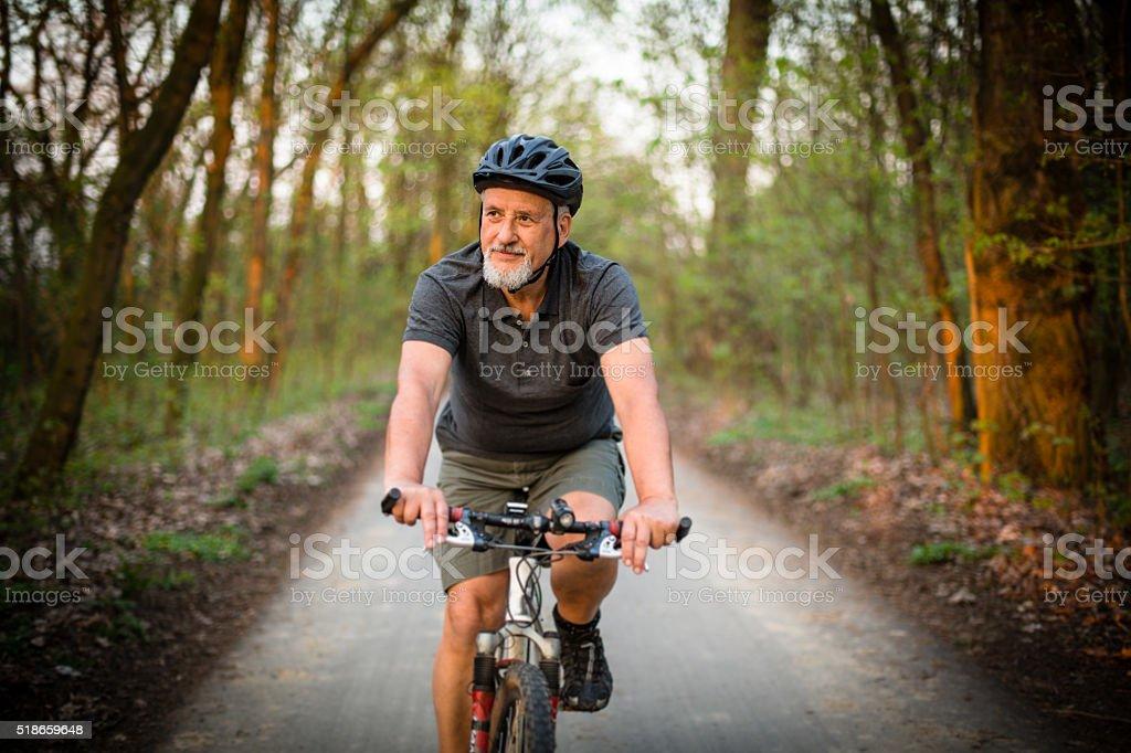 Senior man on his mountain bike outdoors stock photo