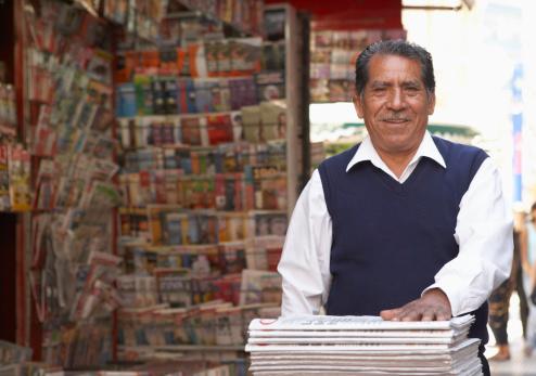 Senior man on newspaper  stand in street, smiling, portrait