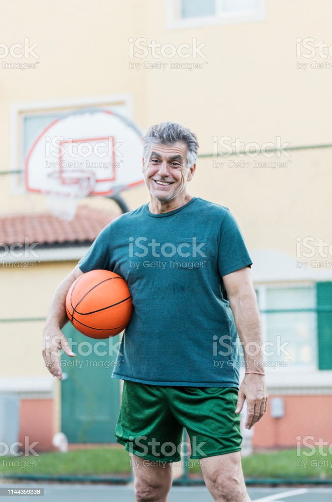 A senior man in his 60s standing outdoors on a basketball court,...