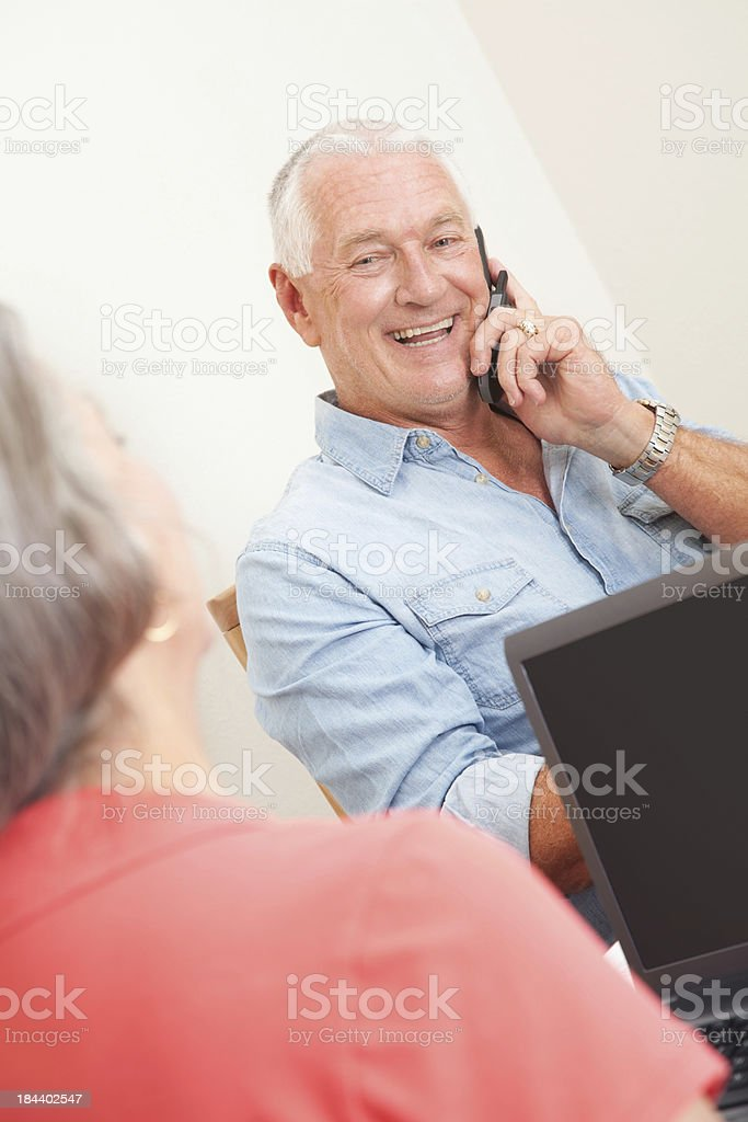 Senior man on phone at home with laptop royalty-free stock photo