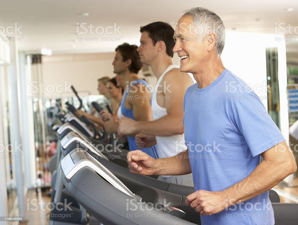 Senior Man On Running Machine In Gym stock photo