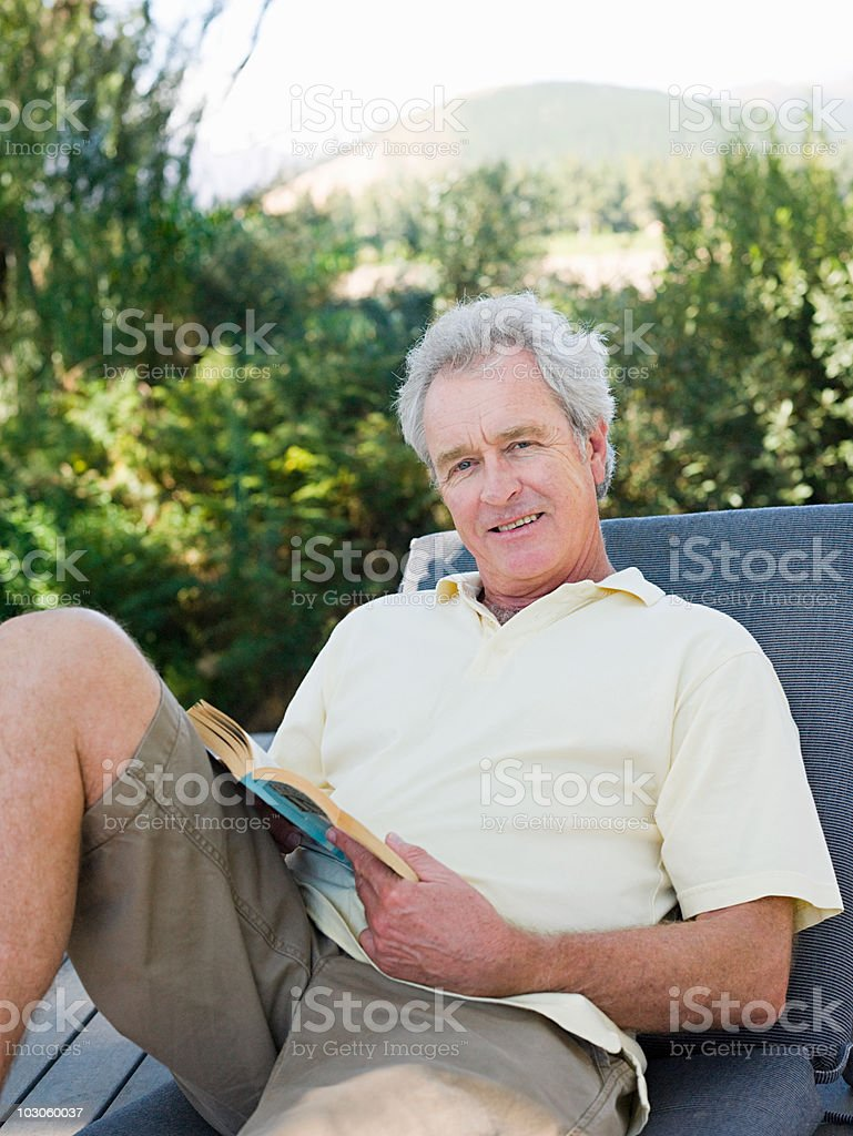 Senior man on sun lounger with book stock photo