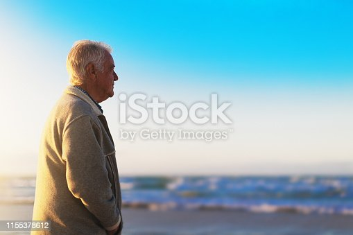 621898406istockphoto Senior man on sunny winter beach gazing out over ocean 1155378612
