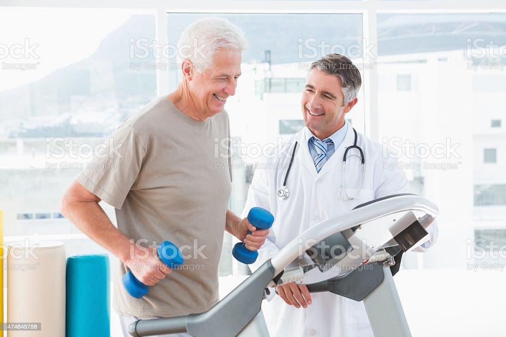 Senior man on treadmill with therapist stock photo