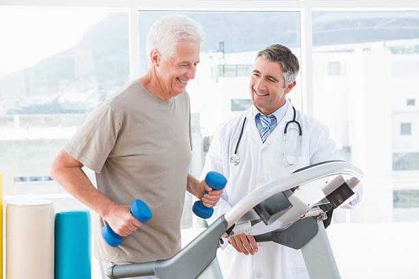 Senior hombre en la cinta trotadora con terapia - foto de stock