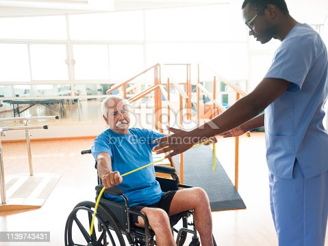 istock Senior man on wheelchair doing exercising for arms 1139743431