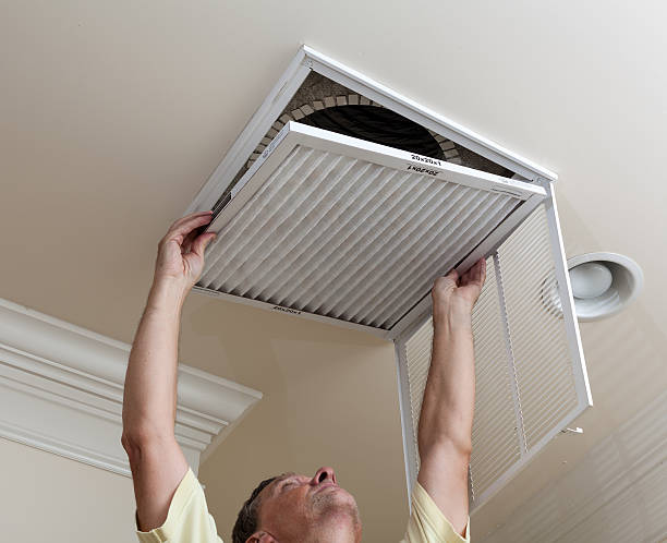 Senior man opening air conditioning filter in ceiling Senior male reaching up to open filter holder for air conditioning filter in ceiling air filter stock pictures, royalty-free photos & images