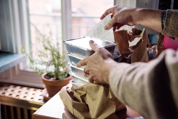 Senior man opening bag of delivered food on counter. stock photo