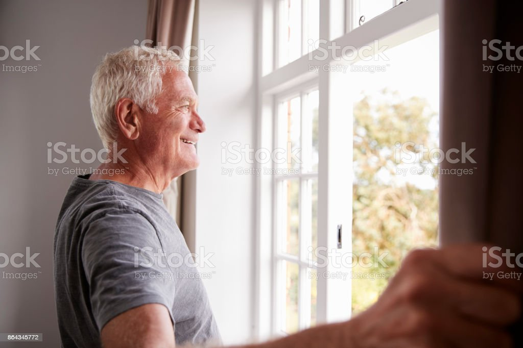Senior Man Opening Bedroom Curtains And Looking Out Of Window royalty-free stock photo