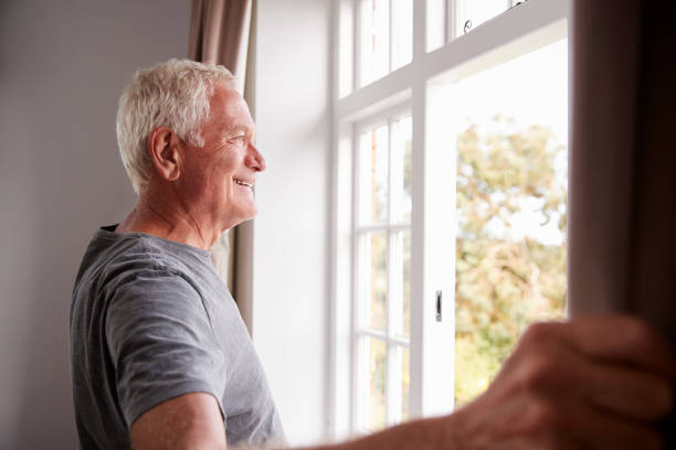 senior man opening bedroom curtains and looking out of window - old men window imagens e fotografias de stock