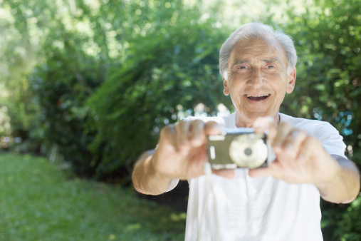 Senior man outdoors holding out digital camera and smiling