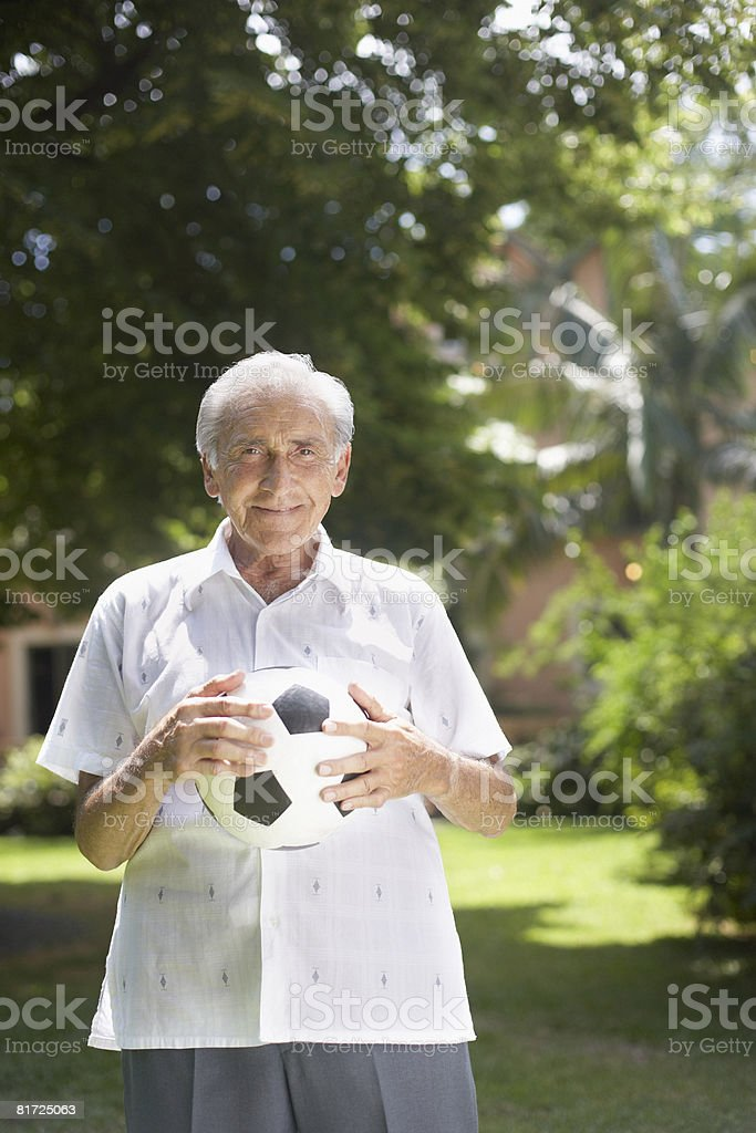 Senior man outdoors holding soccer ball and smiling royalty-free stock photo