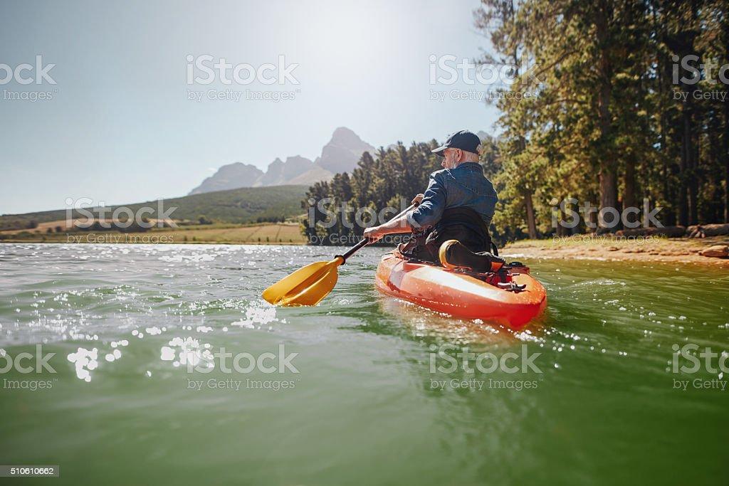 Senior man paddling kayak on a summer day stock photo