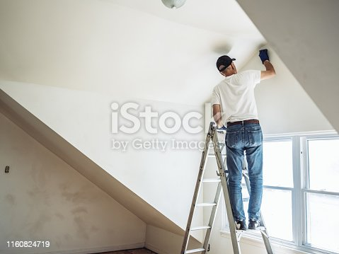 Retirement life. Time to downsize your home. Senior man painting apartment interior.