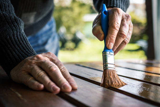 Senior man painting wooden table. Renovation of garden furniture stock photo