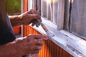 istock Senior man painting wooden windows using paintbrush. Repairing exterior of old house. 1048815502