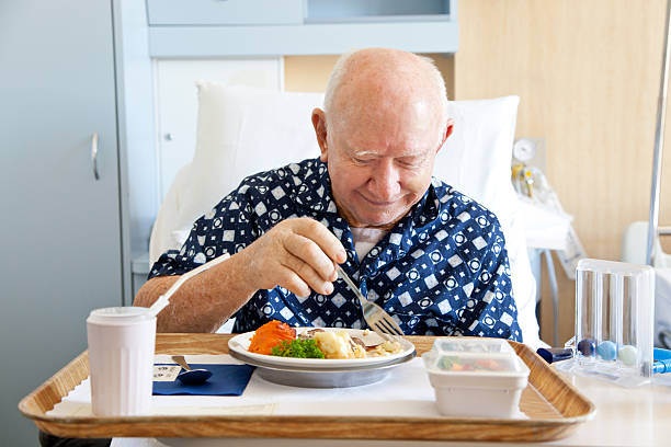 Senior Man Patient in Hospital Bed Eating Meal stock photo