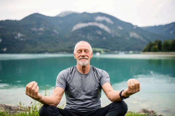 Ein senior man Rentner sitzt am See in der Natur, Yoga-Übung. – Foto