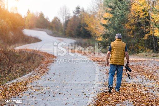 Senior man photographing autumn in road