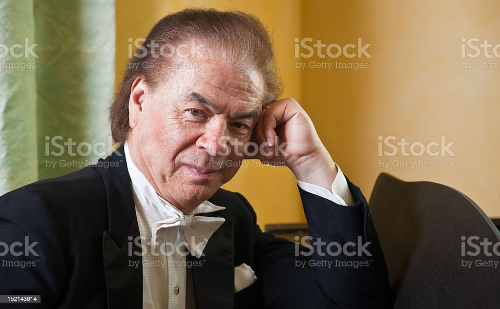 Senior man pianist is sitting next to a grand piano. stock photo
