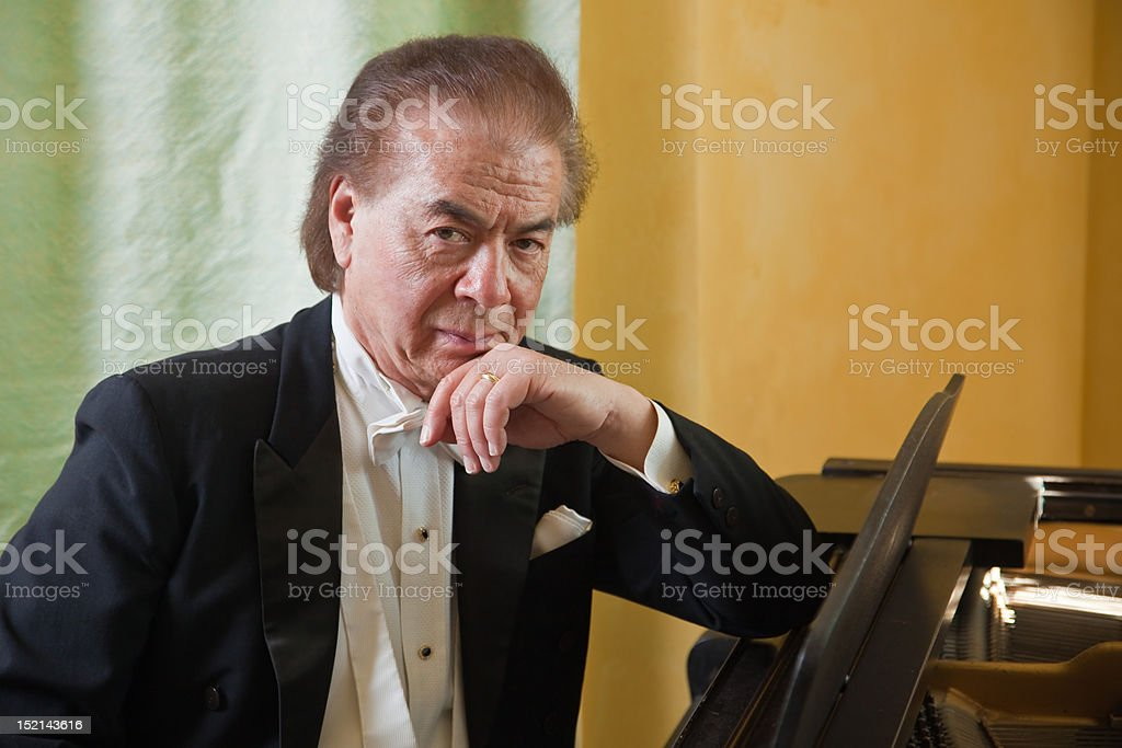 Senior man pianist sitting next to a grand piano. stock photo