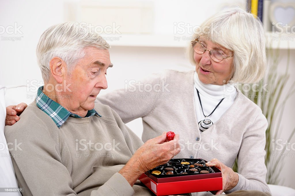 Senior Man Picking Out Chocolate From A Box royalty-free stock photo