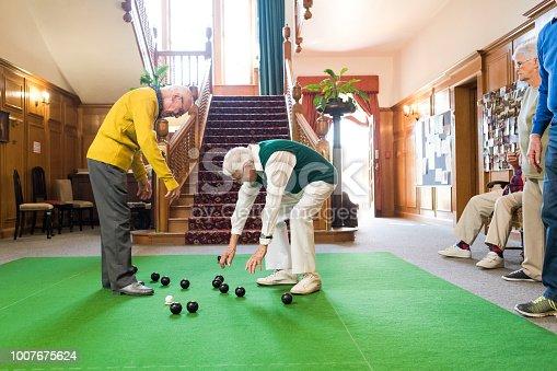 Senior man picking up the bowling balls at a bowls game