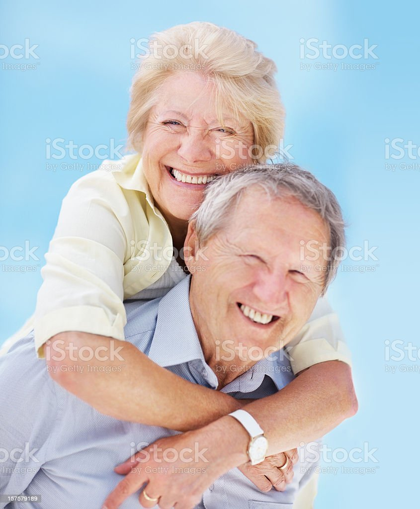 Senior man piggybacking his wife against blue sky royalty-free stock photo