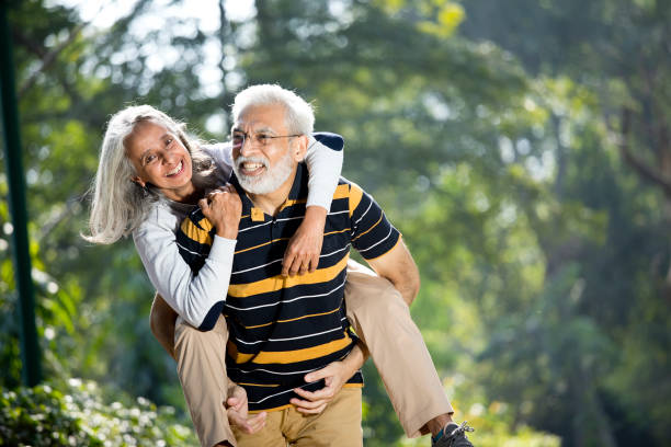 Senior man piggybacking his wife stock photo