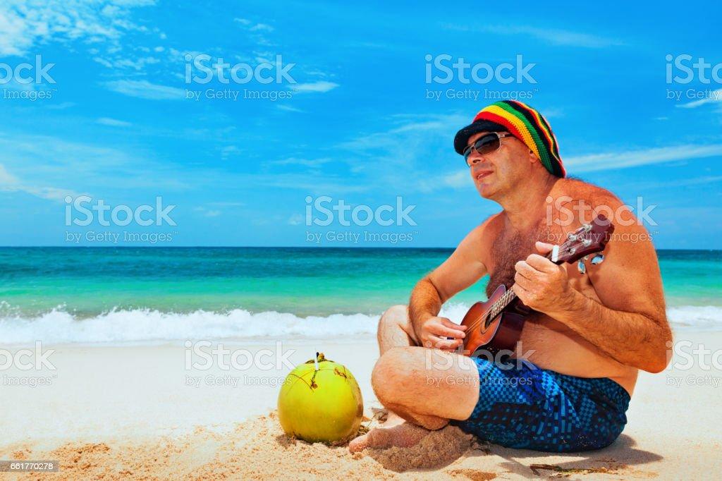Senior man play reggae on Hawaiian guitar on caribbean beach stock photo