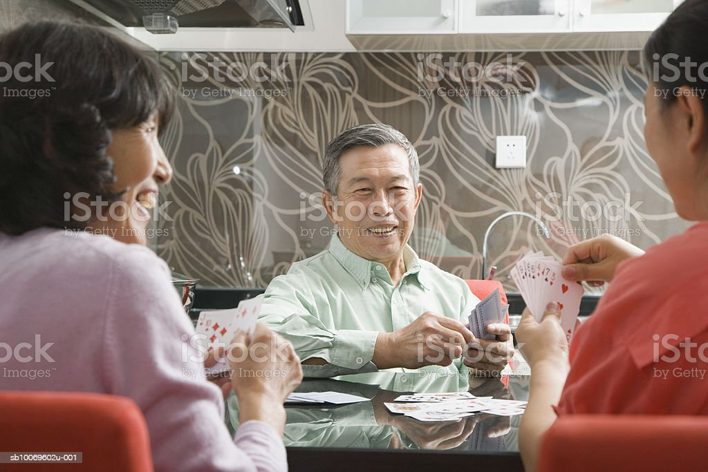 Senior man playing cards with two women foto de stock royalty-free
