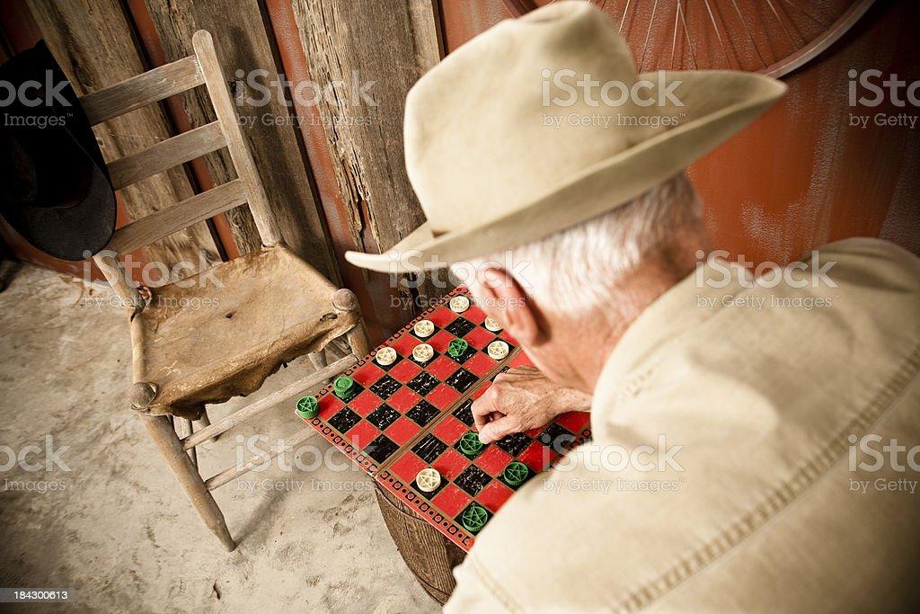 Senior man playing checkers, his partner has left. royalty-free stock photo