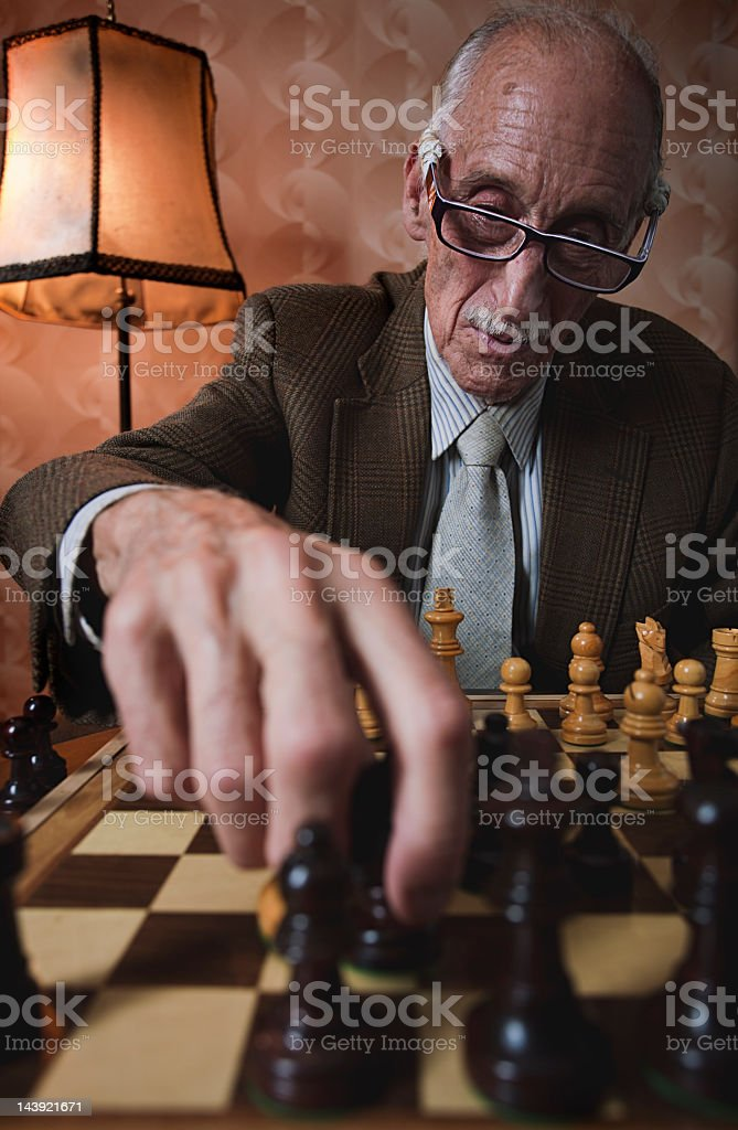 Senior man playing chess _ vertical. royalty-free stock photo