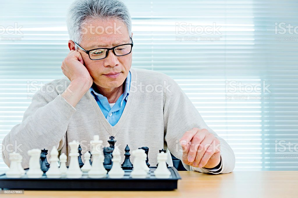 Senior man playing chess stock photo