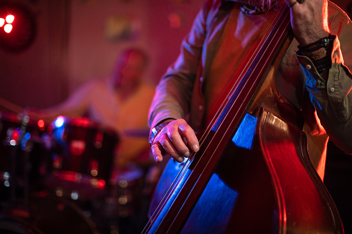 Senior man playing double bass on stage with his band on gig