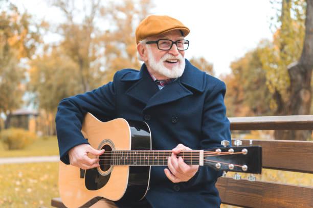 ältere mann an der gitarre zu spielen - werkzeugbank stock-fotos und bilder