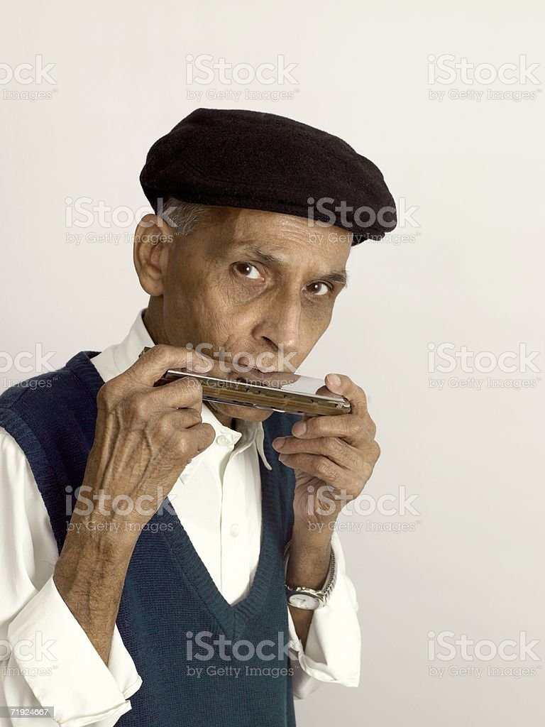 Senior man playing the harmonica stock photo