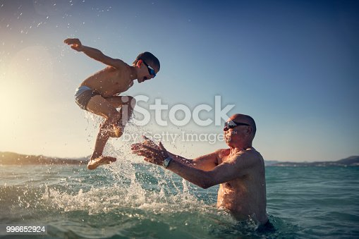 Little boy playing with his grandfather in the sea. The grandfather is tossing the happy boy into the sea. Sunny summer day. Nikon D850